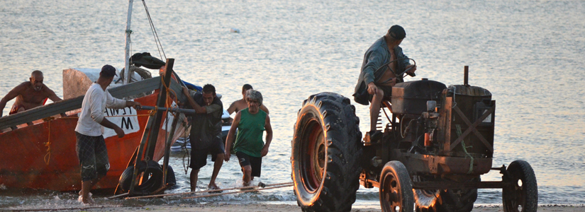 photo of a man on a tractor pulling a boat onto a beach