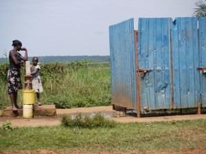 photo of a man and young girl outside a rice storage bin in Kenya
