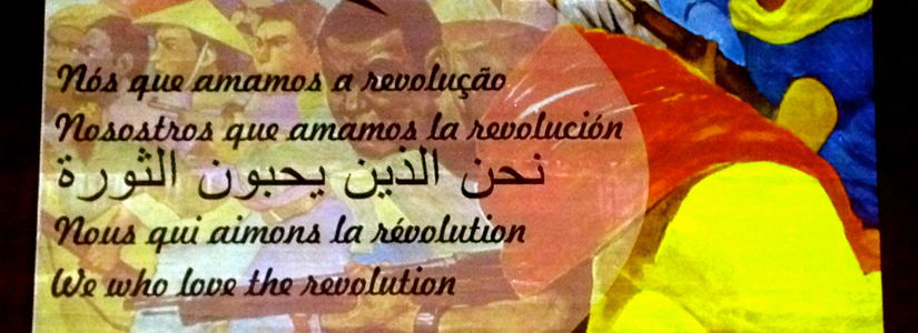 """photo of a sign in multiple languages that says, """"We who love the revolution."""""""