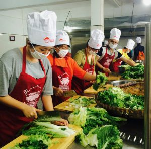 photo of food preparers working on making salads