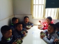 photo of a group of children eating food from bowls while sitting at a table