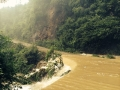 photo of brown water flowing over a road and down an embankment