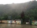 photo of a walled basketball court with lush trees on a hillside in the background