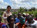 photo of Julie Farzana with a group of people, a settlement is in the background